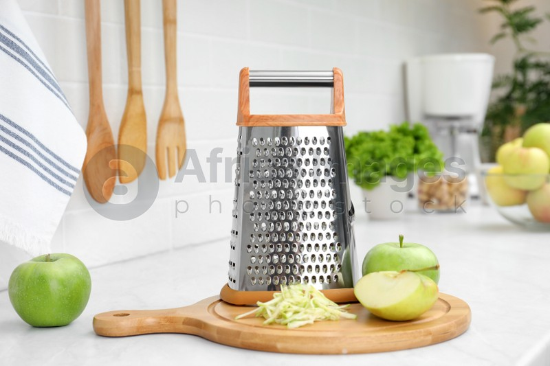 Grater and fresh ripe apples on kitchen counter