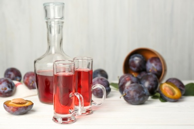 Delicious plum liquor and ripe fruits on white wooden table, space for text. Homemade strong alcoholic beverage