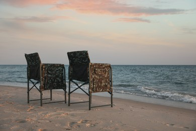 Camping chairs on sandy beach near sea, space for text