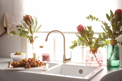 Vases with beautiful protea flowers near sink in kitchen. Interior design