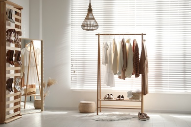 Modern dressing room interior with racks of stylish women's clothes and shoes