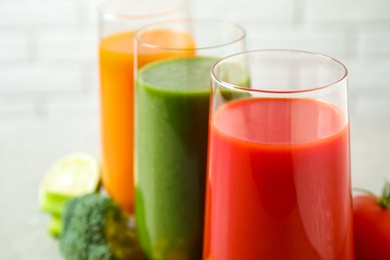 Different tasty juices in glasses, closeup. Space for text