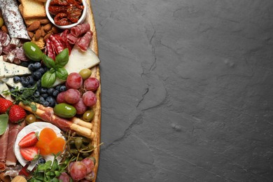 Set of different delicious appetizers served on black table, top view. Space for text