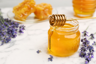Tasty honey and lavender flowers on white marble table, closeup