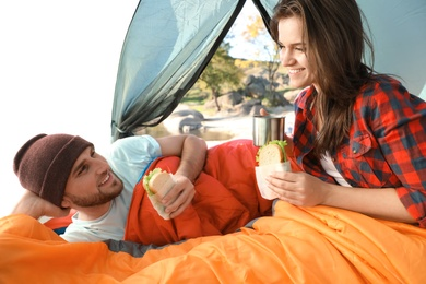 Young couple having breakfast in sleeping bags inside of camping tent