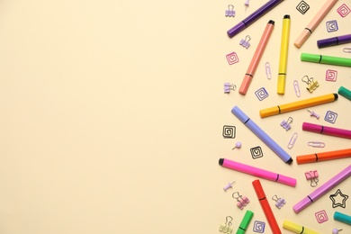 Markers, binders and paper fasteners on beige background, flat lay. Space for text