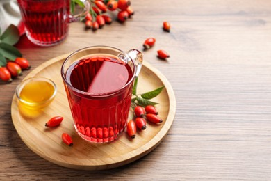 Fresh rose hip tea, honey and berries on wooden table. Space for text