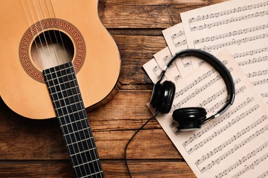 Composition with guitar and music notations on wooden table, flat lay