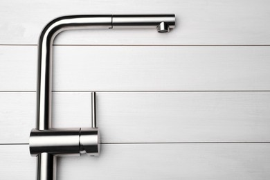 Modern pull out kitchen tap on white wooden table, top view. Space for text