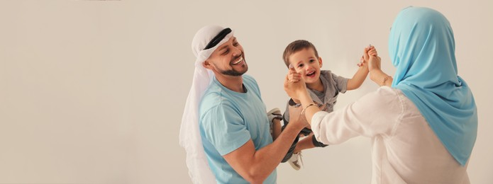 Happy Muslim family spending time together on beige background, space for text. Banner design
