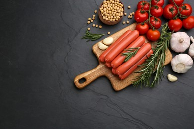 Fresh raw vegetarian sausages and vegetables on black table, flat lay. Space for text