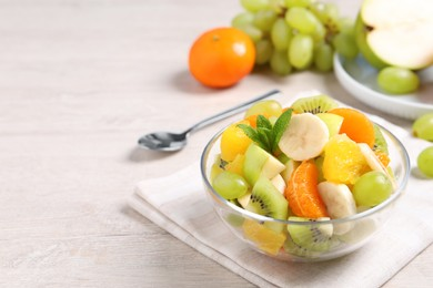 Delicious fresh fruit salad in bowl on table, space for text