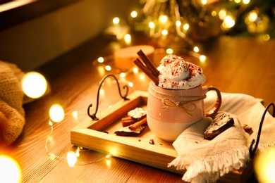 Tasty hot drink with whipped cream and Christmas lights on wooden table