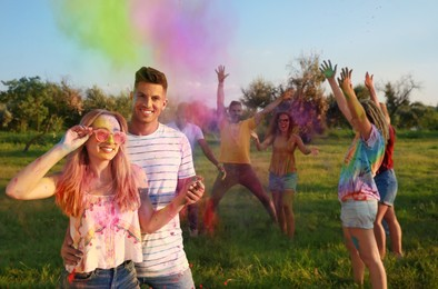 Happy friends with colorful powder dyes outdoors. Holi festival celebration