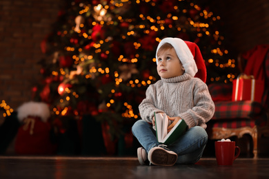 Little boy in Santa Claus cap with book near Christmas tree at home
