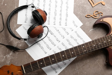 Flat lay composition with music notes, headphones and guitar on color background