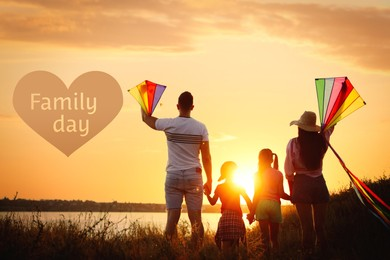 Parents and their children playing with kites outdoors at sunset, back view. Happy Family Day