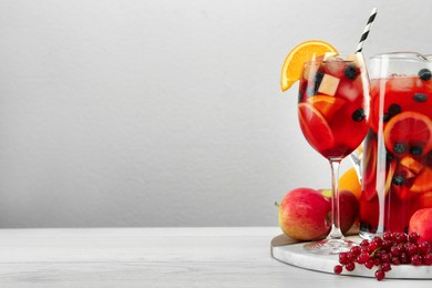 Glass and jug of Red Sangria on white wooden table against light grey background. Space for text