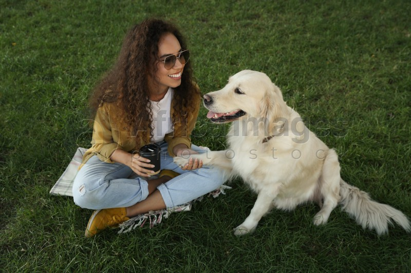 Young African-American woman and her Golden Retriever dog on green grass