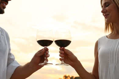 Happy romantic couple drinking wine together on beach, closeup view