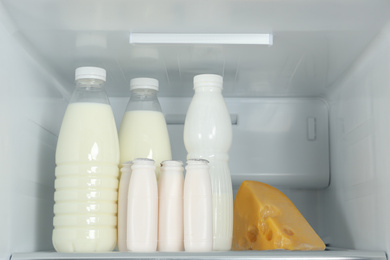 Bottles of dairy products on shelf in refrigerator