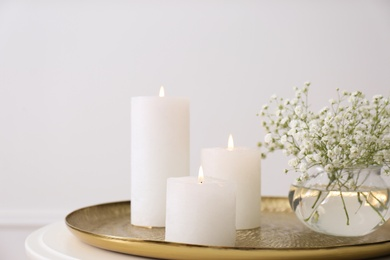 Vase with beautiful flowers and burning candles on table indoors, closeup. Interior elements