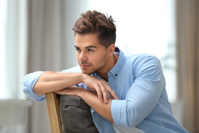 Portrait of handsome young man sitting on chair in room