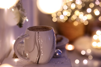Cup of tasty hot drink against blurred Christmas lights. Space for text