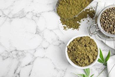 Hemp protein powder, seeds and fresh leaves on white marble table, flat lay. Space for text