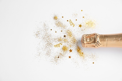 Bottle of champagne with gold glitter and confetti on white background, top view. Hilarious celebration