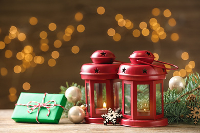Composition with lanterns and decorated fir branches on table against blurred background. Winter holidays