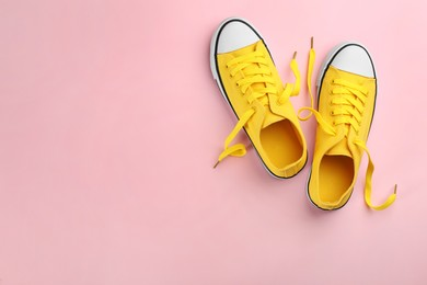 Pair of trendy sneakers on pink background, flat lay. Space for text