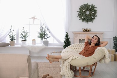 Woman resting in comfortable papasan chair at home