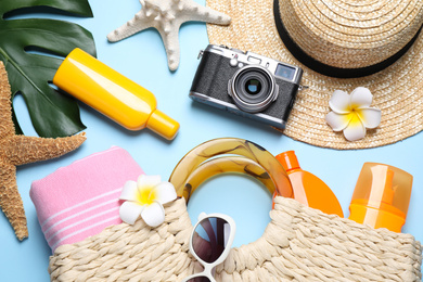 Flat lay composition with sun protection products and beach accessories on light blue background