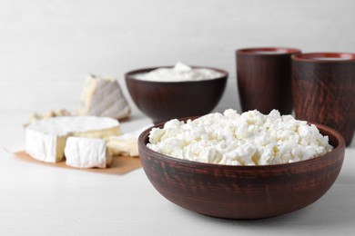 Clay brown bowl with cottage cheese on white wooden table, space for text