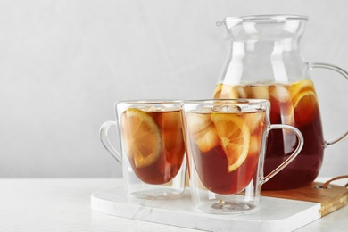 Cups and jug of refreshing iced tea on light table