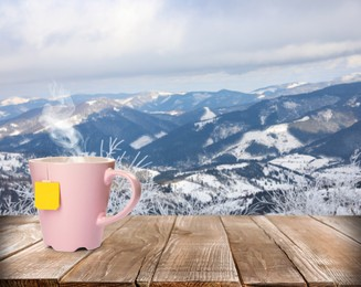 Cup of hot tea on wooden table and beautiful winter landscape on background