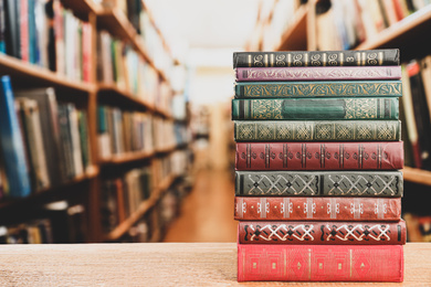 Stack of old vintage books on table in library, space for text