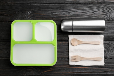 Thermos, lunch box and cutlery on black wooden table, flat lay