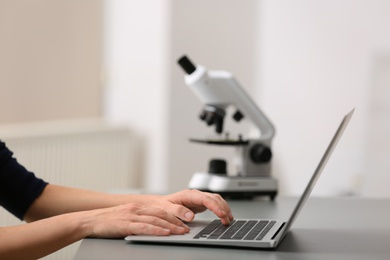 Female student working with laptop at table. Medical education