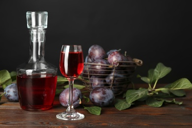 Delicious plum liquor and ripe fruits on wooden table against black background. Homemade strong alcoholic beverage