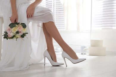 Young bride with bouquet wearing wedding shoes indoors
