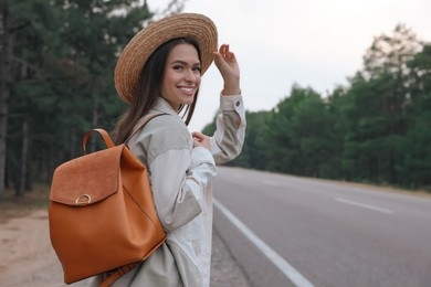 Young woman with stylish backpack near empty road in forest. Space for text