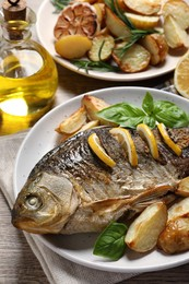 Tasty homemade roasted crucian carp served on wooden table, closeup. River fish
