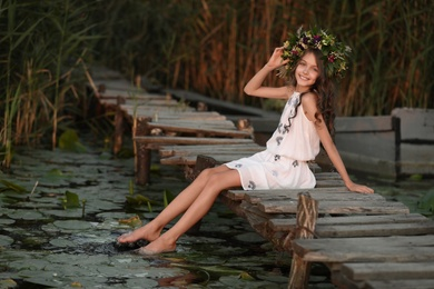 Cute little girl wearing wreath made of beautiful flowers on pier near pond at sunset