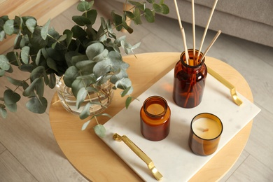 Eucalyptus branches, aromatic reed air freshener and candles on wooden table in living room. Interior element