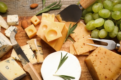 Flat lay composition with different sorts of cheese and knives on wooden table