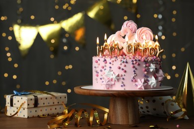 Beautiful birthday cake with burning candles and decor on wooden table. Space for text