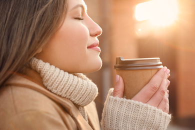 Young woman with cup of coffee on city street in morning, closeup
