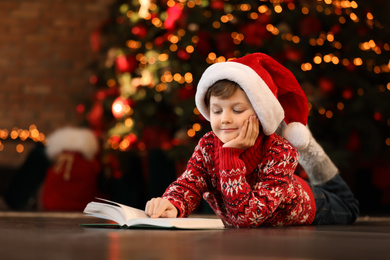 Little boy in Santa Claus cap reading book near Christmas tree at home
